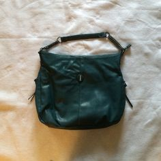 Jennifer Lopez handbag in dark teal This bag has never been used. It has 2 side zip pockets located on the outside of the bag. It has a middle zipped pocket and 2 slip pockets on the inside. There is also a small zipped pocket on the inside. The bag measures approximately 15 inches wide by 15 inches in length (this does not include the handle). The bag is made out of faux leather and the zippers are silver Jennifer Lopez Bags Shoulder Bags