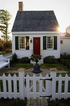Pretty white house with red door and white picket fence. Classic