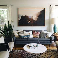 Fantastyczny salon - stonowane, ale starannie dobrane kolory i wzory, trochę zieleni i oversize zdjęcie na ścianie.
