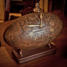 Look at this marvelous rugby-ball-clock! It is of the darkest auburn colours with magically shaped numbers and letters on it and the signs are just like gold!