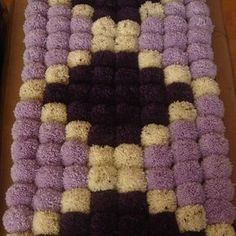 Diamond Pom Pom Rug by Crafty House- This rug is made up of 120 pom pom's in lilac, purple and cream and are arranged in a diamond pattern. The rug measures 85cm x 47cm and comprises 15 rows of Pom Pom's.