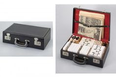 """Fluxkit. 1965, Fluxus Edition announced 1964. Vinyl-covered attaché case, containing objects in various mediums. Designed and assembled by George Maciunas (American, born Lithuania. 1931–1978). 11 x 44 x 28"""" (27.9 x 111.8 x 71.1 cm) (case, closed). 38 x 44 x 28"""" (96.5 x 111.8 x 71.1 cm) (case, open). The Gilbert and Lila Silverman Fluxus Collection Gift"""