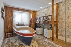 Com inspiração marítima, este dormitório infantil traz elementos que remetem à navegação a partir da cama com estrutura semelhante a um barco. O ambiente une a descontração dos objetos temáticos à elegância da madeira, que impera neste espaço, tornando-o aconchegante e intimista.
