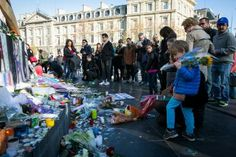 November Terror Attacks in Paris: Advice and Information for Visitors: A child holds flowers as the streets of Paris are quiet surrounding Place de la Republique as France observes three days of national mourning for the victims of the terror attacks on November 15, 2015 in Paris, France. A special service for the families of the victims and survivors is to be held at Paris's Notre Dame Cathedral later on Sunday .