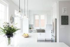 Sleek white kitchen features a trio glass pendants illuminating an L shaped kitchen island topped with white quartz countertops, Caesarstone Calacatta Nuvo Countertops, situated across from an under counter refrigerator and freezer. Kitchen Reno, Kitchen Design, Kitchen Island, Kitchen Ideas, Stainless Steel Apron Sink, Calacatta Nuvo, L Shaped Kitchen, Shaker Cabinets, Transitional Kitchen