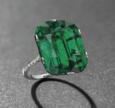 Ring Set with a cushion-shaped emerald, weighing approximately 23.28 carats, to the diamond line shoulders, mounted in platinum