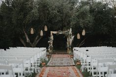 Boho ceremony site with rugs, lanterns + a pampas grass chuppah