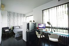 A custom-made divider with a swivel TV separates the sleep space from the work space.