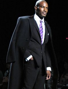 Tyson Beckford. Love the suit, tie and the coat but please take a moment to put the coat on your not a hanger. :))