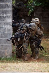 U.S. Marines with Company E, Battalion Landing Team, 2nd Battalion 4th Marines, 31st Marine Expeditionary Unit (MEU), look around a corner during a vertical assault as part of the MEU Exercise (MEUEX), in Combat Town, Okinawa, Japan, Dec 10, 2014. BLT 2/4 is conducting training in preparation of their upcoming spring patrol. (U.S. Marine Corps photo by GySgt Ismael Pena/Released)