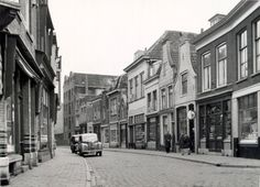 Beschrijving: De zuidzijde van de Dam, gezien vanaf de hoek met de Breedstraat (op de voorgrond links, niet te zien).