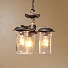 "Suspended by rope-wrapped rods and rigged with 3 clear glass cylinder shades (included), this convertible chandelier can hang down over a kitchen table or close up to the ceiling in a mudroom. From coastal kitchens to rustic family rooms, you'll feel like just sailing into the sunset! 3x60 watts (medium base sockets). Fixture comes with 6 feet of chain and 10 feet of wire. (15.25""Hx15""W)6' of chain and 10' of wire."