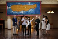 Artist Yoko Ono (C), widow of John Lennon, reacts next to Irish singer Bono (3rd R) and guitarist The Edge of U2 (3rd L) during the unveiling of a tapestry honoring Lennon at Ellis Island in New York July 29, 2015. REUTERS/Eduardo Munoz