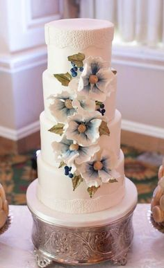 Elegant white wedding cake with pretty blue and white flowers; Featured Photographer: Melanie Rebane Wedding Photography, Cake: Sophie Bifield Cake Company