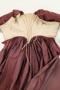 Inside look, robe à la polonaise, late 1770s. Shot mauve/grey silk taffeta, with boned, low pointed back panels, internal skirt loops, sleeves with double tiered embroidered muslin engeants, linen lining.