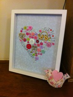 These button pictures are handmade using a wide variety of buttons, gems and wooden embellishments. They can be personalised with silver sparkly wording or one initial and will…