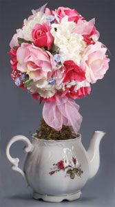 A burst of  bright silk flowers affixed atop a delicately-painted teapot, this topiary makes a beautiful centerpiece. Display with our Teacup Roses Topiary!