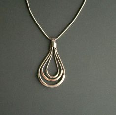 Modernist snake chain necklace with clean, minimal pendant. Three cased, concentric, snake chain droplets from a spare bail. Pendant glides along a slippery snake chain. Finished at the ends with a simple spring ring closure. In very good condition. Unsigned.    18.5 inches - $60
