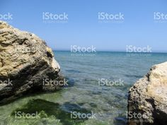 Two Beige-brown rocks are symmetrical around the edges of the photo, and between them the blue-turquoise sea royalty-free stock photo by #ioanna_alexa