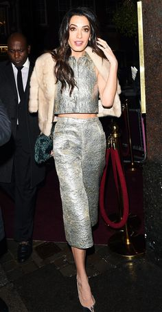 Amal Clooney wears a silver jacquard crop top with matching culottes, a cropped fur jacket, and silver pumps