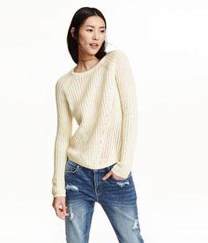 En ribbstickad tröja i mjuk bomullsblandning. Tröjan har lång raglanärm och något längre bakstycke.