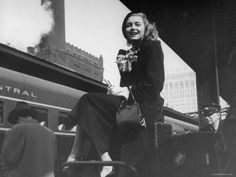 Actress Patricia Neal Sitting on Her Luggage on the Platform of a Train Station During a Stopover