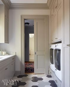 Andrew Howard Interior Design - A pocket door opens to a chic laundry room filled with gray shaker cabinets adorned with polished hardware topped with white marble fitted with a sink.