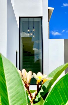 Cubic white modern house with large opening and pendant light on stairs