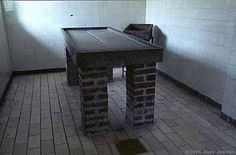 """Mauthausen. A dissecting table. Among many other pseudo-scientific """"experiments"""", SS doctors removed organs from living people, bottled and stored them on shelves in the dissecting room. They skinned prisoners with interesting tattoos and sold them as book covers, gloves, luggage and lamp shades. One physician selected two prisoners with near perfect teeth and used their heads as paperweights on his desk."""