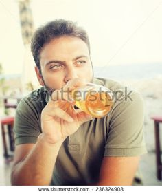 Young man drinking beer sitting at the restaurant near the sea.