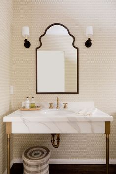 Links in Latte by Galbraith and Paul covers the walls of the powder room. Hodges designed the vanity and chose a Moorish-inspired Moroccan mirror from Wisteria and Marlo sconces by Kerry Joyce for Palmer Hargrave. The fixtures are Newport Brass.