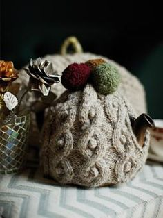 This cabled tea cosy is topped with cute pom poms and has been designed by Martin Storey using Lima.