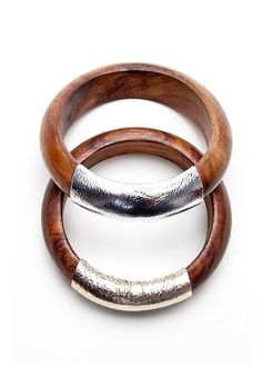 "Hand-carved and locally sourced leather provide for a pretty bangle set. The long tradition of Indian wood carving is used to handcraft two wide bangles. The top part is curved into a smooth shape, with the inside laying flat. Metallic gold and silver leather adorn the respective bangle. The natural wood creates an earthy appeal while the leather adds a contemporary aesthetic. The final result is a modern bohemian bangle set. Dimensions: 2.5"" inner diameter x .75"" H Care + Maintenance…"