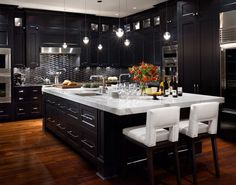 Elegant Kitchen Design with Black Cabinets, Marble Countertop, Armless Chairs, Beautiful Lamps, and Hardwood Floor