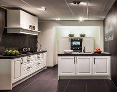 Een modern landelijke keuken met zwarte accenten. De grepen zijn uitgevoerd in de kleur zwart, net zoals dit het geval is bij de apparatuur en het werkblad. Deze keuken is naast wit ook leverbaar in de kleuren magnolia en kristal.