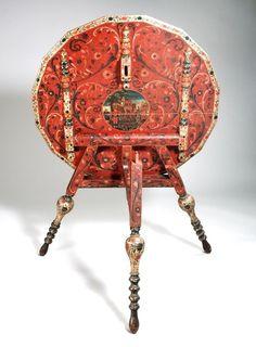 Flap-aan-de-wand beschilderd met bijbelse voorstelling   Deze klaptafel uit Hindeloopen is aan de onderkant van het tafelblad beschilderd met een voorstelling van de verheffing van Jozef in een medaillon. Rondom de bijbelse voorstelling is het tafelblad #druk versierd met krullen.    Maker: P.I.?   Verv.jaar: 1700 - 1800   Techniek: beschilderd   Object: meubilair
