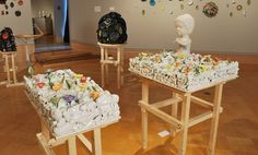 Porcelain figures placed in a landscape of broken, cast porcelain objects and cast porcelain flowers and leaves, supported on plywood pedestals.