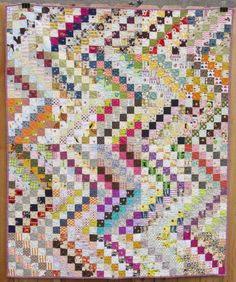 Scrappy quilt, made from 6x6 postage stamp blocks with dominant dark center strip, pieced together for zig zag effect.