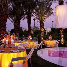 Brides.com: Whimsical Retro Wedding Style. Sixties Sass  What's the desert without heat? Uplighting turns this palm-ringed lawn into a glam coconut grove; the sparks are strictly up to you.  Flowers, R. Jack Balthazar Fêtes et Fleurs. Lighting, Barker Décor Service.