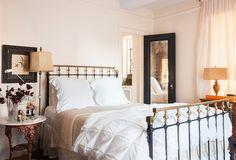 Mixed metals including a bronze spray-painted table that Smith borrowed from her grandfather and an antique queen-size bed create a feminine look in the master bedroom.