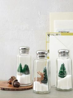 """Turn under-a-dollar salt shakers into mini winter wonderlands by nesting toy evergreens and deer atop iodized """"drifts."""""""