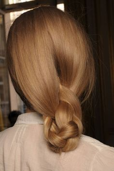 Braided low ponytail tucked into a semi-chignon