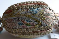Creation Date:   sixteenth century  Materials:   Dimensions:   4.0 x 4.5 x 4.5 cm  RCIN   37040  Description:     A silk, silver and gold thread needlework pomander purse, covered in needlework of floral design with a gold fringe and drawstring with four tassels.