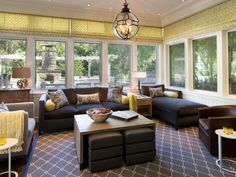 This white sunroom is livened by pops of light green, which highlight the great outdoor view provided by the wrap-around windows.