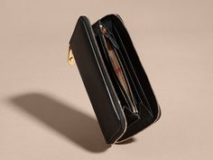 A wallet worked in grainy Italian leather. The decorative zip closure recalls the epaulettes on our classic trench coat, and keeps coins and cards secure on the move.