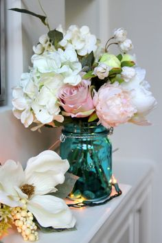 Love this elegant silk arrangement in a blue colored glass mason jar. Creamy white hydrangeas, pale pink austria roses and one large creamy white