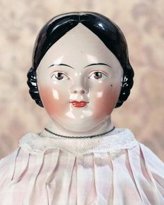 """German Pink-Tinted Porcelain Doll with Brown Eyes 24"""" (61 cm.) Pink tinted porcelain shoulder head with sculpted black hair arranged in short finger curls,painted brown eyes,single stroke black brows,accented nostril circles,red and black upper eyeliner,closed mouth with center accent line,muslin stitch-jointed body,porcelain lower limbs,painted blue boots,antique costume and undergarments. Condition: generally excellent. Comments: Germany,circa 1865."""