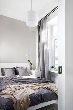 Grey Scandinavian style bedroom - I love here grey curtains and grey bedding with orange throw that adds a little bit of life into monochrome scheme.