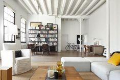 loft-industriel-salon-avec-canapé-blanc-cassé-fauteuil-blanc-table-basse-bois-bibliotheque-metal-noire-poutres-apparentes-blanches-bibliotheque-noire