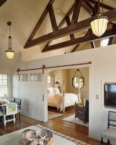 Palatial Farmhouse Living Room with Sliding Barn Door Bedroom Divider - by C.H. Newton Builders, Inc